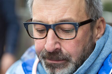 Street portrait of middle aged man with glasses.