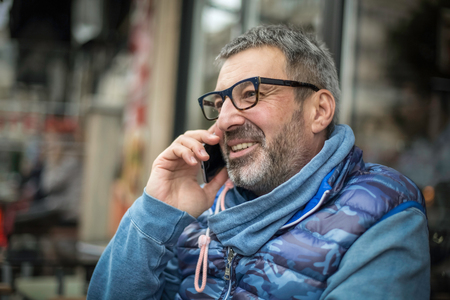 Middle-aged man with a gray beard and urban glasses, talking on a mobile phone