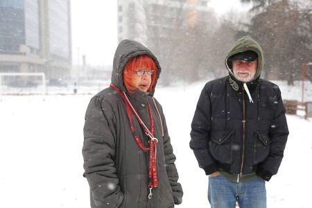 Man and woman in senior years walking on blizzard day in park. Weather concept.