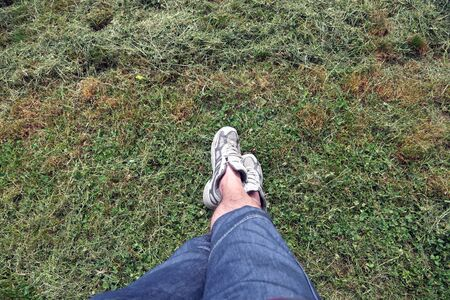 Grass texture with man in sneakers in summer Stok Fotoğraf