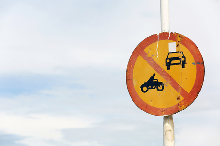 Old rusty traffic sign forbids motor vehicle on road.