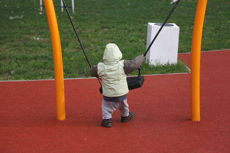 Little boy in autumn jacket swinging on swing at playground.