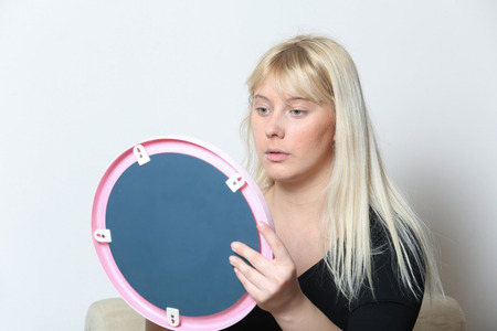 Blond girl adjusting her makeup in front of a mirror in her room.
