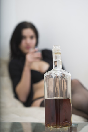 Indoor photo of bottle of alcohol with sexy girl in black provocative lingerie on blurry background. Stok Fotoğraf
