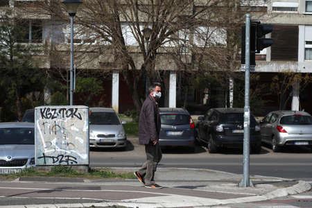 BELGRADE, SERBIA - MARCH 28, 2020: Man with mask in street. As the Corona Virus continues to spread all over Serbia, government imposed curfew to prevent the spread of coronavirus disease, during the day  people can only go outside for existential things  Redakční