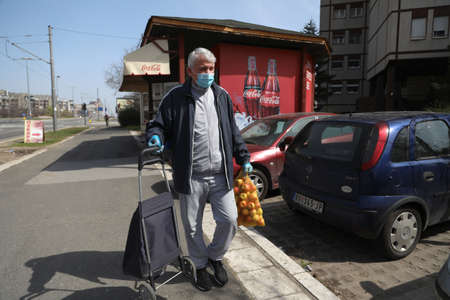 BELGRADE, SERBIA - MARCH 28, 2020: Man in a mask carries a bow. As the Corona Virus continues to spread all over Serbia, government imposed curfew to prevent the spread of coronavirus disease, during the day  people can only go outside for existential thi Redakční