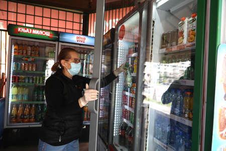 BELGRADE, SERBIA - MARCH 28, 2020: Saleswoman at workplace traffic. As the Corona Virus continues to spread all over Serbia, government imposed curfew to prevent the spread of coronavirus disease, during the day  people can only go outside for existential