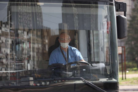 BELGRADE, SERBIA - MARCH 28, 2020: The bus driver with a mask. As the Corona Virus continues to spread all over Serbia, government imposed curfew to prevent the spread of coronavirus disease, during the day  people can only go outside for existential thin Stock Photo - 144180563