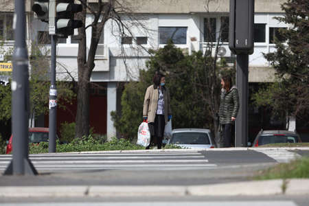 BELGRADE, SERBIA - MARCH 28, 2020: Two woman talking in the street. As the Corona Virus continues to spread all over Serbia, government imposed curfew to prevent the spread of coronavirus disease, during the day  people can only go outside for existential Redakční