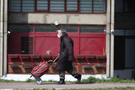 BELGRADE, SERBIA - MARCH 28, 2020: Old woman in the street. As the Corona Virus continues to spread all over Serbia, government imposed curfew to prevent the spread of coronavirus disease, during the day  people can only go outside for existential things