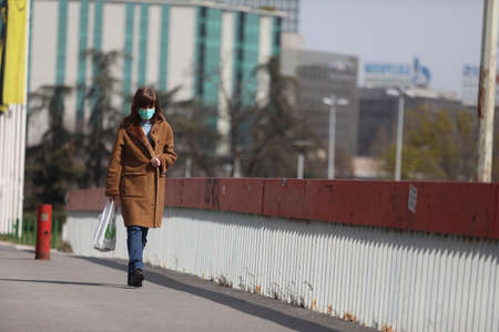 BELGRADE, SERBIA - MARCH 28, 2020: Woman with mask walking in sthe street. As the Corona Virus continues to spread all over Serbia, government imposed curfew to prevent the spread of coronavirus disease, during the day  people can only go outside for exis