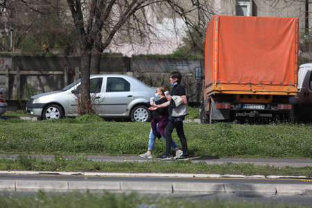 BELGRADE, SERBIA - MARCH 28, 2020: Couple with mask walking in the street. As the Corona Virus continues to spread all over Serbia, government imposed curfew to prevent the spread of coronavirus disease, during the day  people can only go outside for exis Redakční