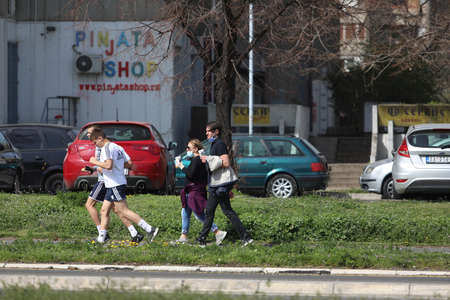 BELGRADE, SERBIA - MARCH 28, 2020: People in the street. As the Corona Virus continues to spread all over Serbia, government imposed curfew to prevent the spread of coronavirus disease, during the day  people can only go outside for existential things suc Redakční