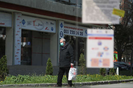 BELGRADE, SERBIA - MARCH 28, 2020: Man with mask. As the Corona Virus continues to spread all over Serbia, government imposed curfew to prevent the spread of coronavirus disease, during the day  people can only go outside for existential things such as wo