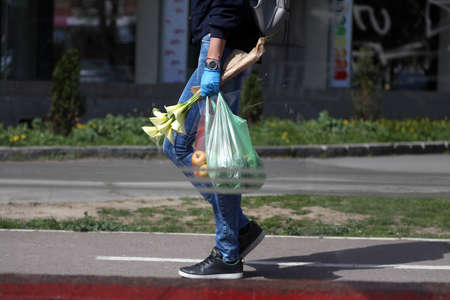 BELGRADE, SERBIA - MARCH 28, 2020: Woman with surgical gloves and food. As the Corona Virus continues to spread all over Serbia, government imposed curfew to prevent the spread of coronavirus disease, during the day  people can only go outside for existen