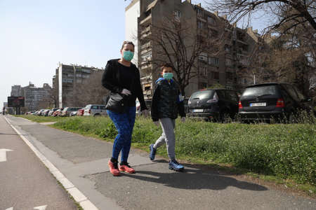BELGRADE, SERBIA - MARCH 28, 2020: Family in street. As the Corona Virus continues to spread all over Serbia, government imposed curfew to prevent the spread of coronavirus disease. Redakční