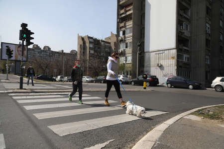 BELGRADE, SERBIA - MARCH 28, 2020: Family in street with dog. As the Corona Virus continues to spread all over Serbia, government imposed curfew to prevent the spread of coronavirus disease.