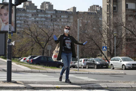 BELGRADE, SERBIA - MARCH 28, 2020: Girl with mask in street. As the Corona Virus continues to spread all over Serbia, government imposed curfew to prevent the spread of coronavirus disease.