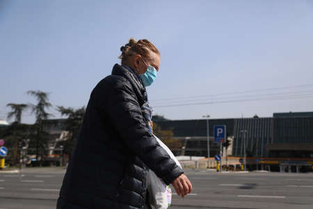 BELGRADE, SERBIA - MARCH 28, 2020: Older woman in street. As the Corona Virus continues to spread all over Serbia, government imposed curfew to prevent the spread of coronavirus disease. Redakční