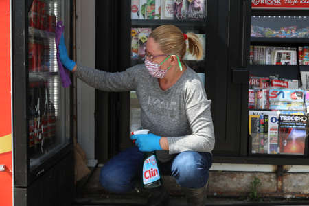 BELGRADE, SERBIA - MARCH 28, 2020: Worker woman cleans the window. As the Corona Virus continues to spread all over Serbia, government imposed curfew to prevent the spread of coronavirus disease.