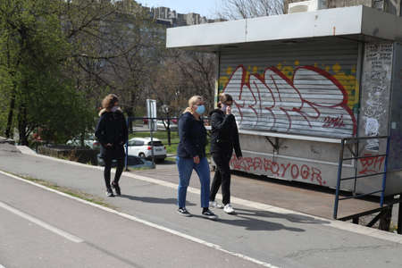 BELGRADE, SERBIA - MARCH 28, 2020: Mom walking with children. As the Corona Virus continues to spread all over Serbia, government imposed curfew to prevent the spread of coronavirus disease.