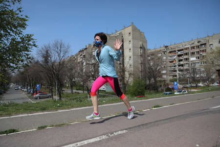 BELGRADE, SERBIA - MARCH 28, 2020: Woman running on street. As the Corona Virus continues to spread all over Serbia, government imposed curfew to prevent the spread of coronavirus disease.