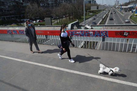 BELGRADE, SERBIA - MARCH 28, 2020: Woman with child and dog. As the Corona Virus continues to spread all over Serbia, government imposed curfew to prevent the spread of coronavirus disease. Redakční