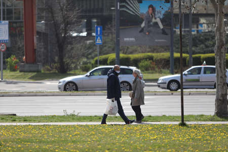 BELGRADE, SERBIA - MARCH 28, 2020: Man an woman in street. As the Corona Virus continues to spread all over Serbia, government imposed curfew to prevent the spread of coronavirus disease.