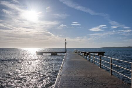 Cala Millor pier at dawn on a sunny day. Mediterranean Sea. Island of Mallorca, Spain