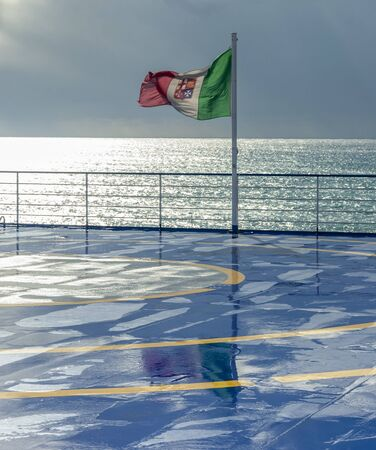 Italian flag flying in the wind with the Mediterranean Sea in the background