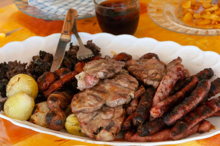 Barbecued meat. Pork loin, sausages, black pudding and vegetables on a white plate