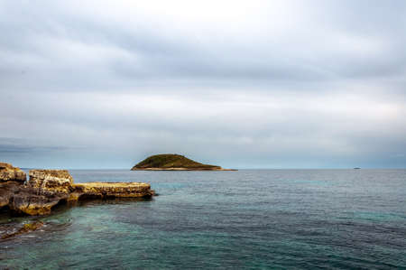 Sa Porrassa Island seen from Magaluf beach on a cloudy day