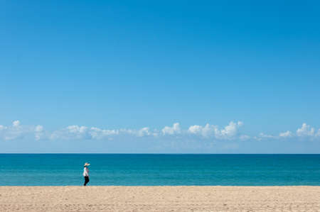 Unrecognizable person walking on a totally empty beach in Mallorca on a summer day Imagens