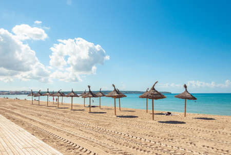 Palma beach with umbrellas and without hammocks. Tourist crisis in Spain due to Coronavirus