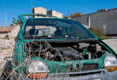 Abandoned green car and scrapped in an abandoned lot. Vandalism image