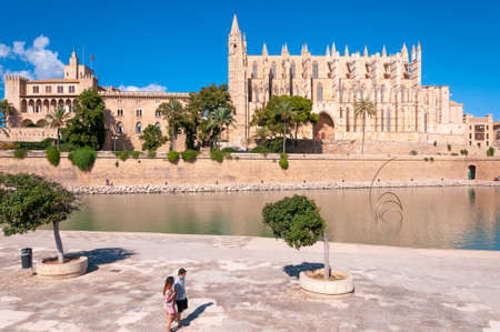 Palma de Mallorca, Balearic Islands / Spain; September 2020: Parc de la Mar. In the background Palma Cathedral and the Almudaina Palace. In the foreground two tourists with a face mask Editorial