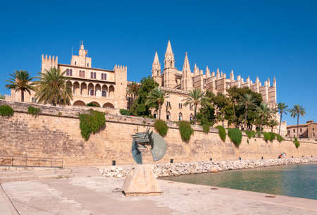 Palma de Mallorca, Balearic Islands / Spain; September 2020: Parc de la Mar. In the background Palma Cathedral and the Almudaina Palace. In the foreground a bronze sculpture