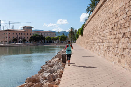 Palma de Mallorca, Balearic Islands / Spain; September 2020: woman running along the walls of the Parc de la Mar on a sunny summer afternoon. Island of Mallorca Editorial