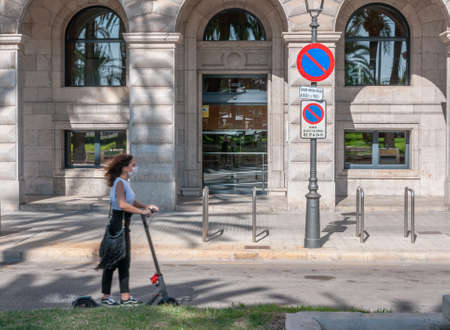 Palma de Mallorca, Balearic Islands / Spain; September 2020: teenager using an electric scooter and face mask, unfocused by the movement of the scooter, circulating in the historic center of Palma Stok Fotoğraf - 159000831