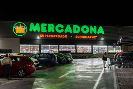 Campos, Balearic Islands / Spain; november 2020: night image of the parking lot and the green luminous sign of a Spanish supermarket chain