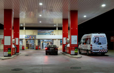 Campos, Balearic Islands / Spain; November 2020: night image of a service station and vehicle refueling. Users refueling an ambulance and a car at the gas station Stok Fotoğraf - 159001096