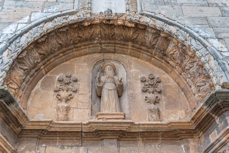 Campos, Balearic Islands / Spain; November 2020: stone arch with religious sculpture outside the church in the Majorcan town of Campos Stok Fotoğraf - 159001230