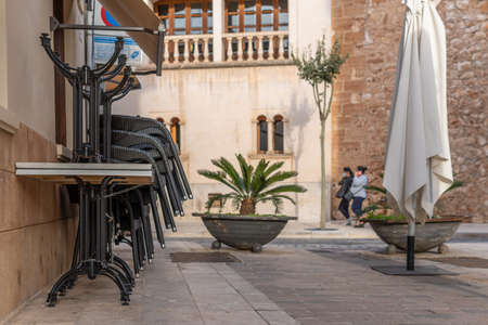 Campos, Balearic Islands / Spain; November 2020: commercial street in the town of Campos, with the terrace of a closed cafeteria. Chairs and tables tied with a chain. In the background two women Stok Fotoğraf - 159001273