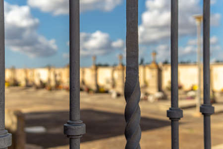 Metallic fence that delimits a cemetery. In the background, unfocused tombs with a bokeh effect. Island of Mallorca, Spain Stok Fotoğraf - 158942680