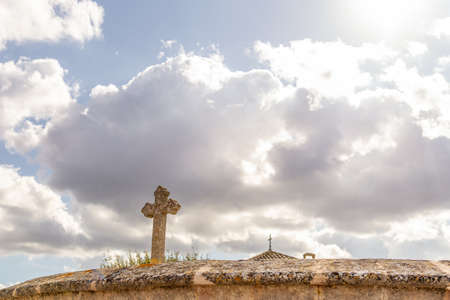 Stone cross located on the perimeter of a religious cemetery, on a sunny day. Island of Mallorca, Spain Stok Fotoğraf