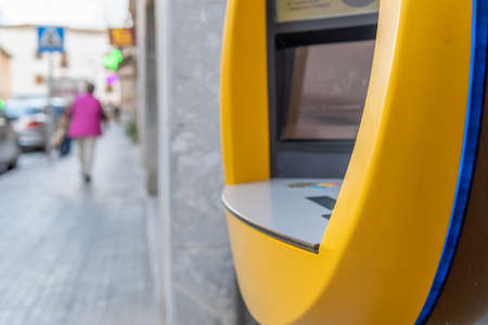 Campos, Balearic Islands / Spain; November 2020: Detail of an ATM of a Spanish private bank. In the background, the street with unfocused people Stok Fotoğraf - 159071990