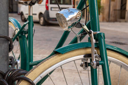 Detail of an old green bicycle, parked in the street with the background out of focus
