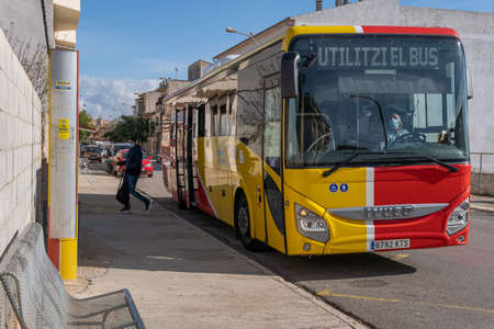 Campos, Balearic Islands / Spain; November 2020: bus of line of the island of Majorca that unites the towns with the capital. Bus stop in the town of Campos. Driver with face mask Stok Fotoğraf - 159072028