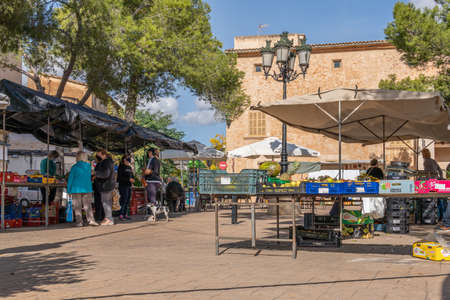 Campos, Balearic Islands / Spain; November 2020: fruit and vegetable stall at the traditional street market in Campos. Seller and buyers with facial masks for the new social measures by the Covid-19 Stok Fotoğraf - 159072280