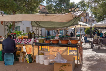Campos, Balearic Islands / Spain; November 2020: fruit and vegetable stall at the traditional street market in Campos. Seller and buyers with facial masks for the new social measures by the Covid-19 Stok Fotoğraf - 159072281